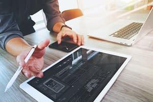 Real Internet Website designer working digital tablet and computer laptop and digital design diagram on wooden desk as concept